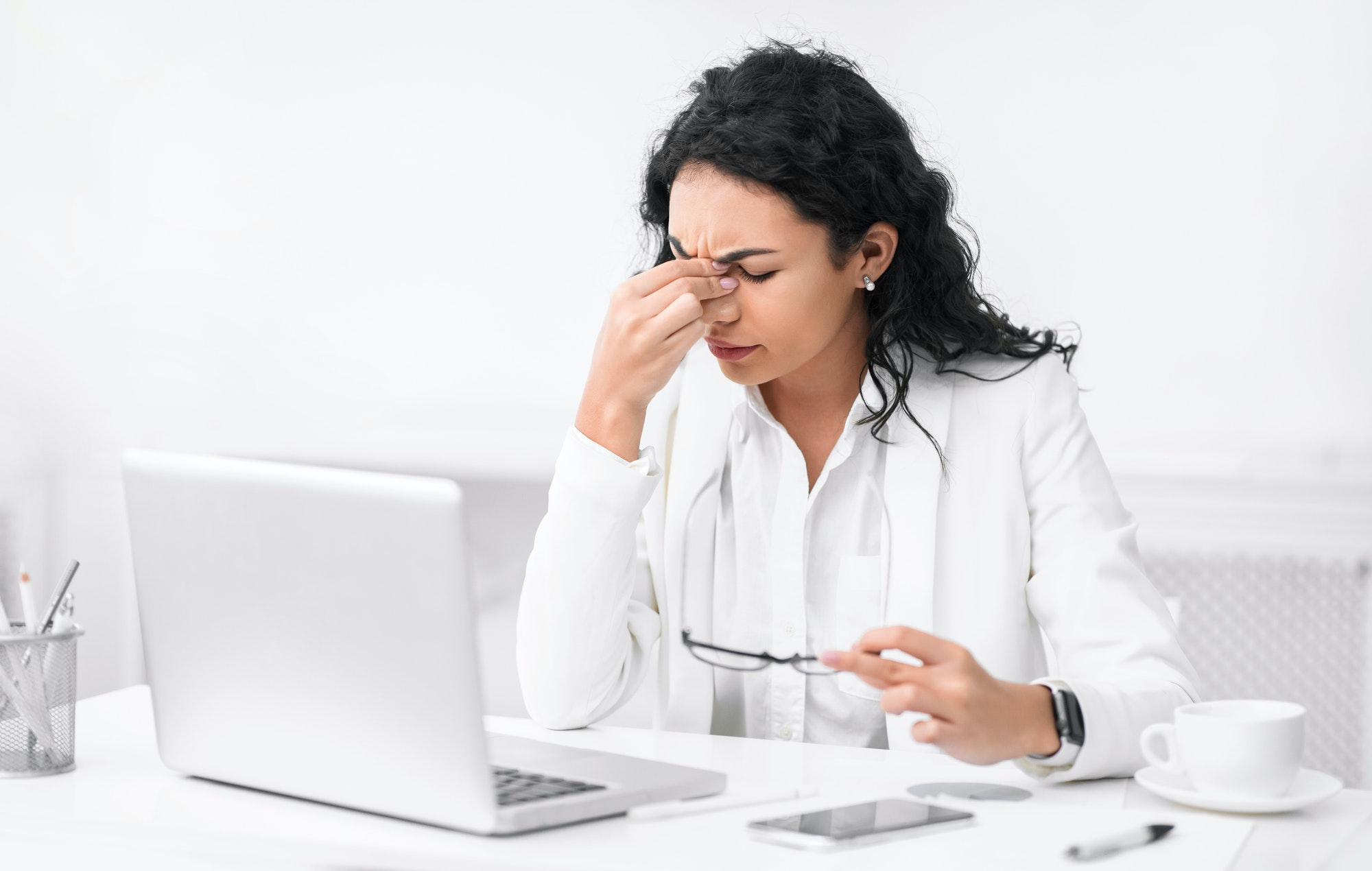 Exhausted latin manager massaging nose while using laptop